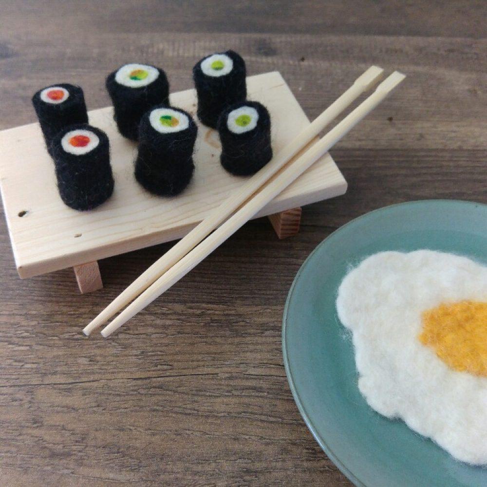 sushi van vilt op een plankje ernaast een gebakken ei van vilt